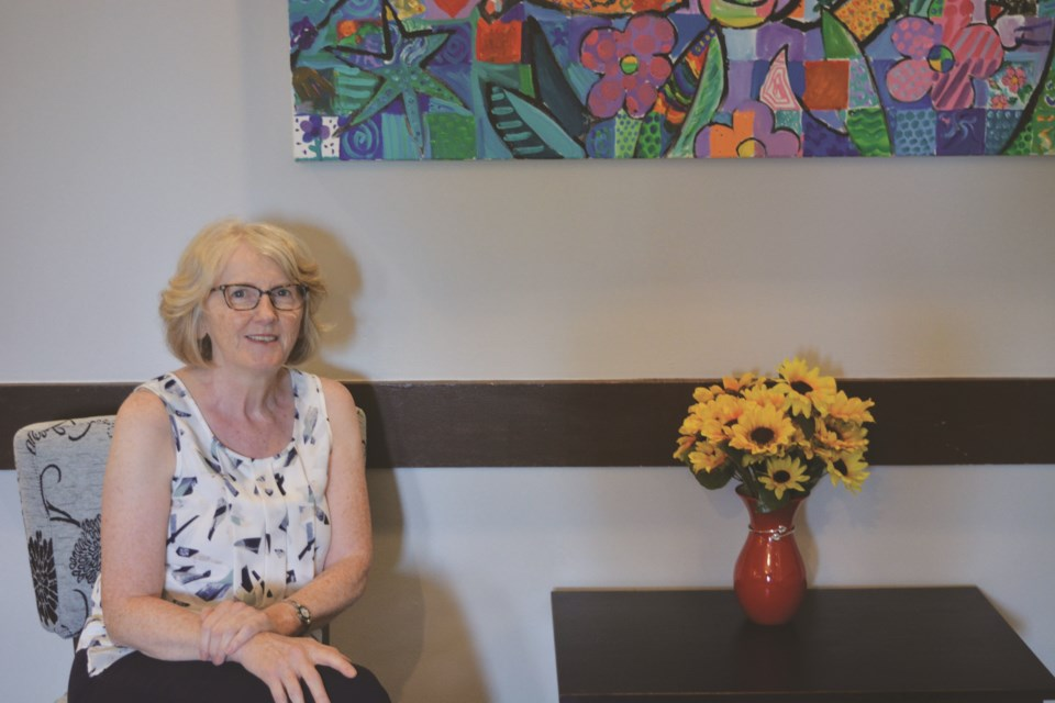 Karen MacDonald poses in the new home of Ladies Out Loud, a group she founded to bring awareness and create a sense of community for local women.