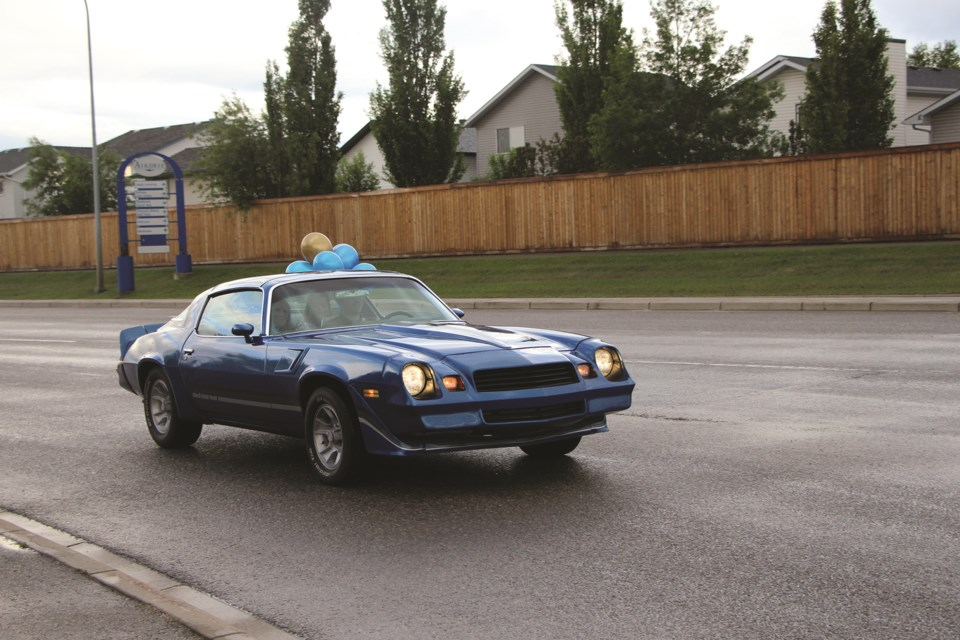 A classic car leads a procession of vehicles down 8 Street in Airdrie on June 5 in celebration of their Grade 12 graduation.