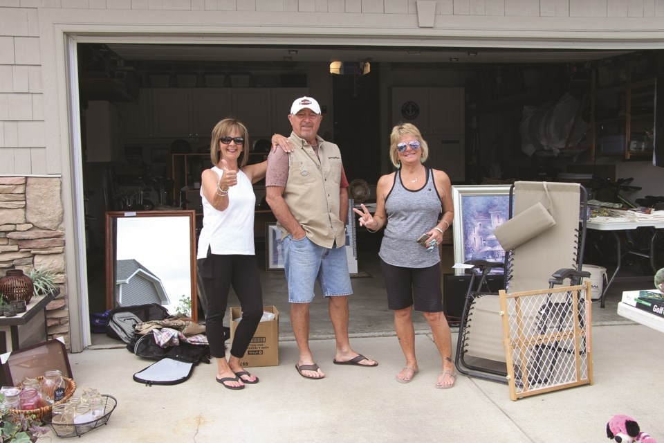 Airdrie residents Kathy Vitale (left), Jeff Vitale (centre), and Roma Gallant (right) pose in front of what is left for sale after a busy garage sale weekend. Photo by Carmen Cundy/Airdrie City View