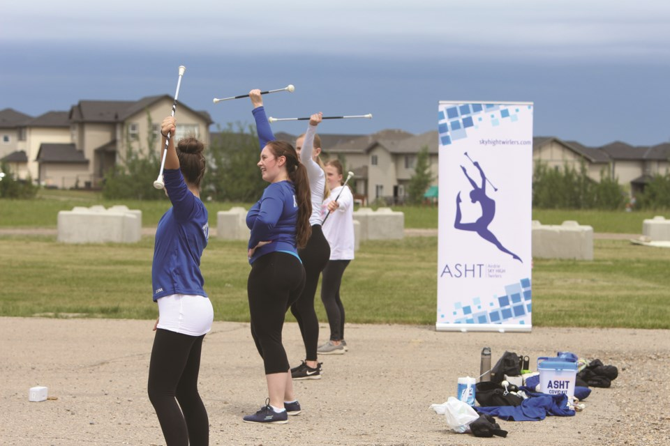 Coaches and instructors lead participants in a baton twirling clinic in the parking lot of Day Break Community Church on June 19.