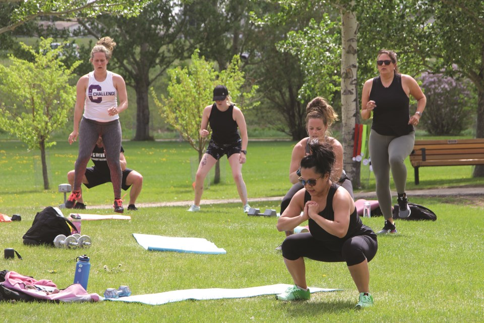 A participant in an outdoor fitness class at Nose Creek Regional Park is seen squatting as part of a series of exercises on June 5. Photo by Carmen Cundy/Airdrie City View