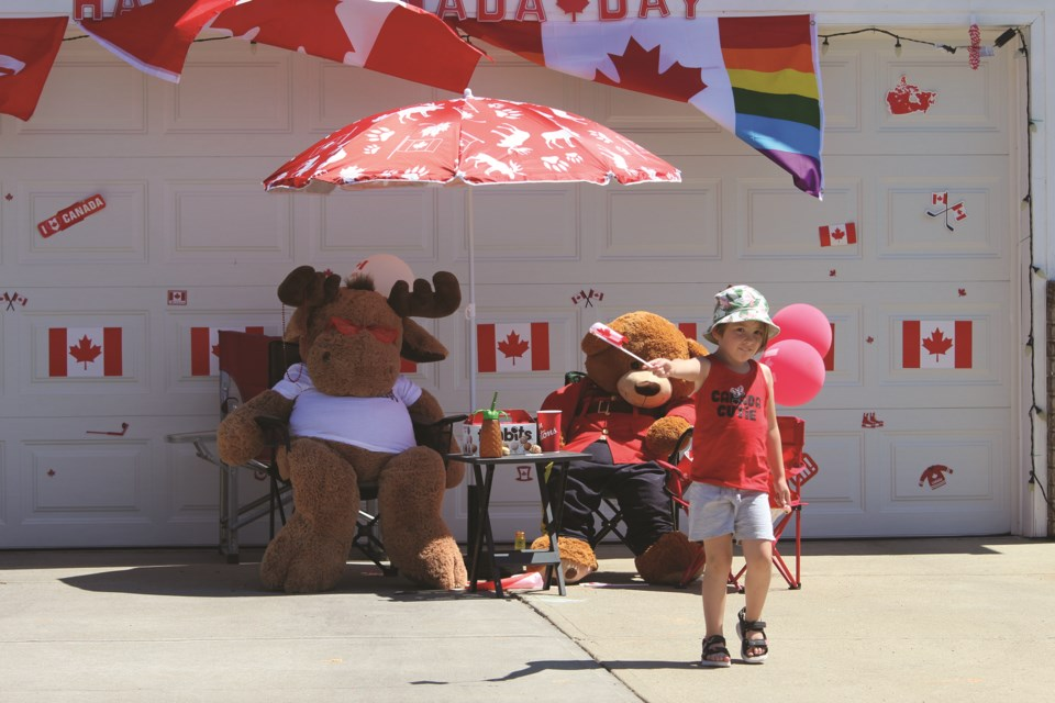 A Canada Day celebrant offers passersby a Canadian flag in front of his home, decorated for Airdrie's Canada Day house-decorating competition.