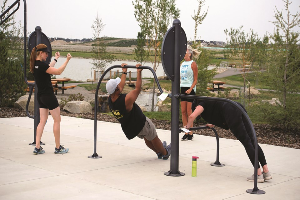 A group of people exercise using the outdoor gym equipment at the new Bayview Park in southwest Airdrie.