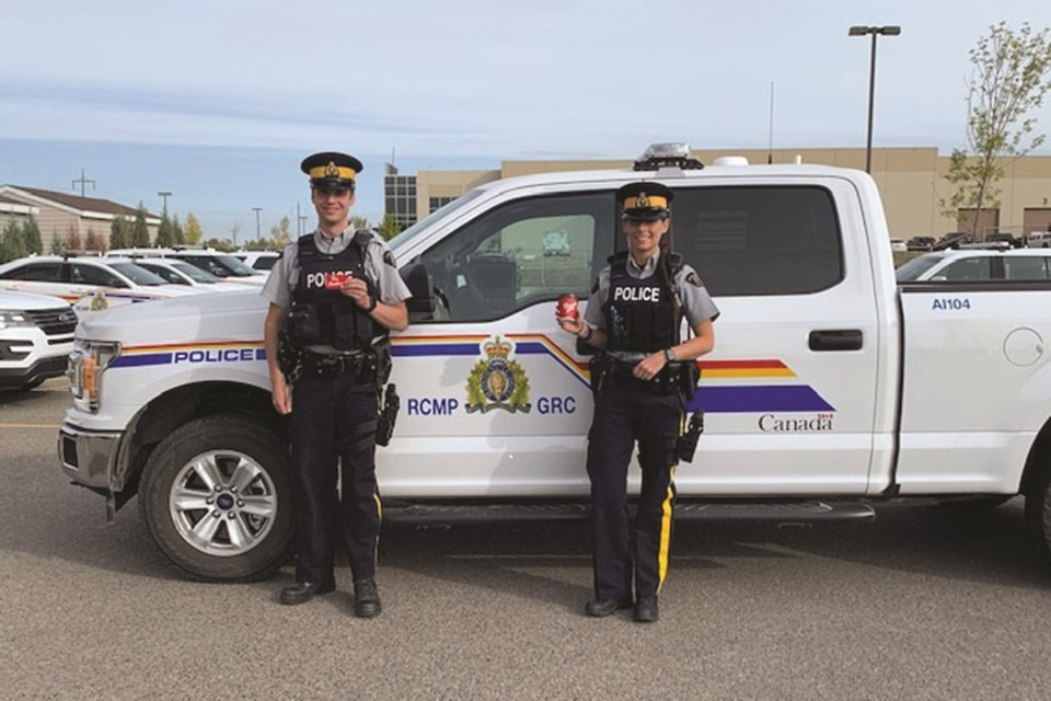 Airdrie RCMP officers were surprised Sept. 22 when local teenagers provided them with some Tim Hortons gift cards in the detachment parking lot. Photo submitted/For Airdrie City View.