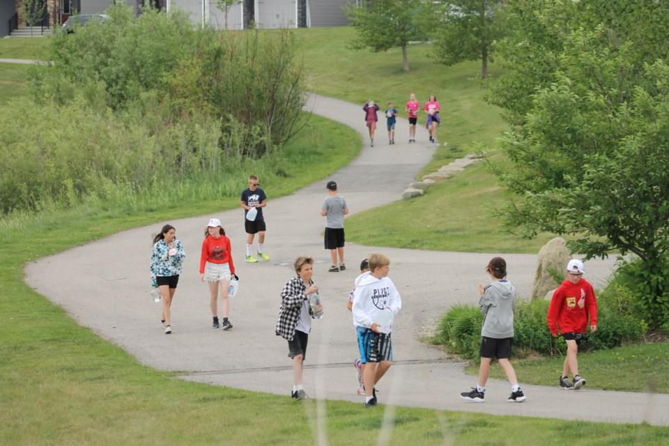 Students in Chelsey Schubert's Grade 6 class at Northcott Prairie School walk around the Hillcrest pond on June 23.