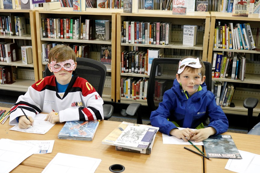 Donning masks, these two superheroes were busy creating their very own comic books at Airdrie Public Library during Free Comic Book Day May 4. Nathan Woolridge/Rocky View Publishing
