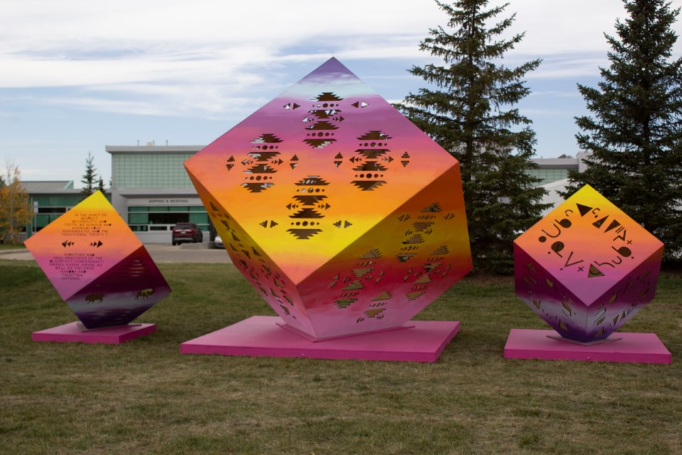 The exhibit consists of three colourful cubes bearing Indigenous land acknowledgments.