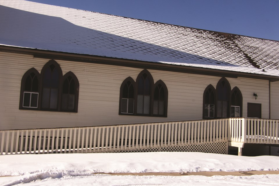 Stained glass windows are overshadowed by an Airdrie church building's reflection as the sun shines on Feb. 27.