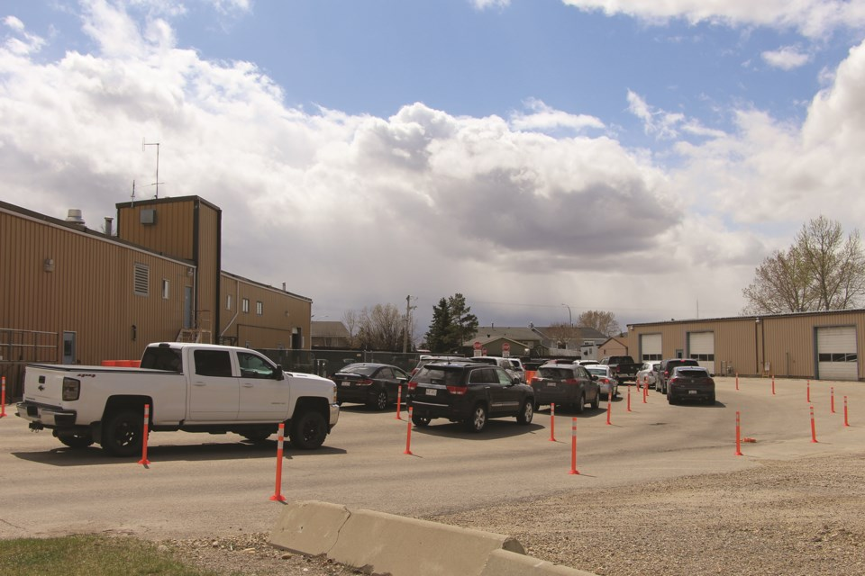 Vehicles line up at in Airdrie on May 1 to get tested for COVID-19. A rapid increase in cases in the city has created a larger demand for the city's testing facility.