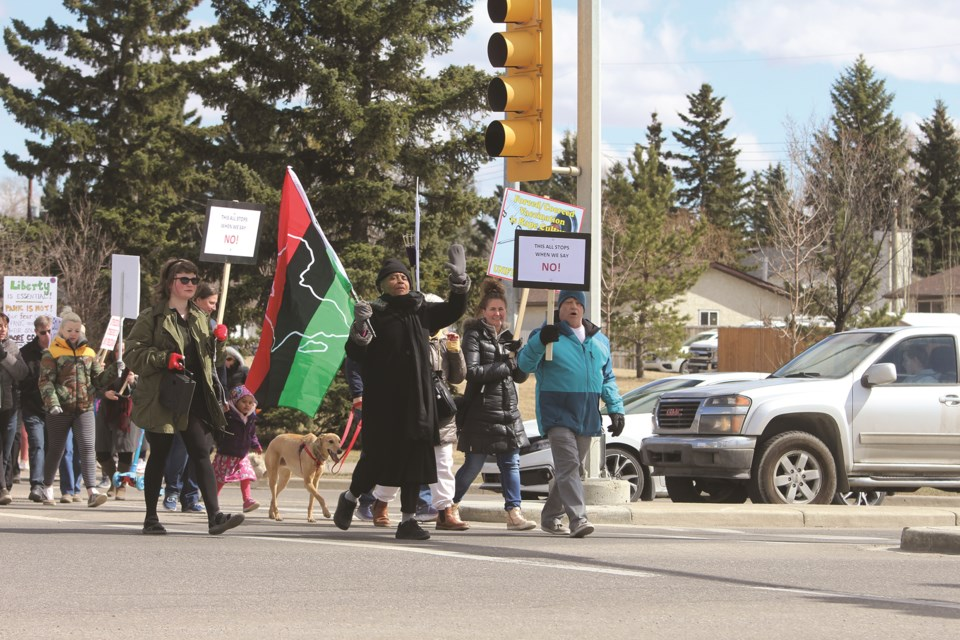 Protesters cross the intersection between Main Street and Veteran's Boulevard holding various signs, including anti-mask and anti-lockdown signs on April 11. Carmen Cundy/Airdrie City View