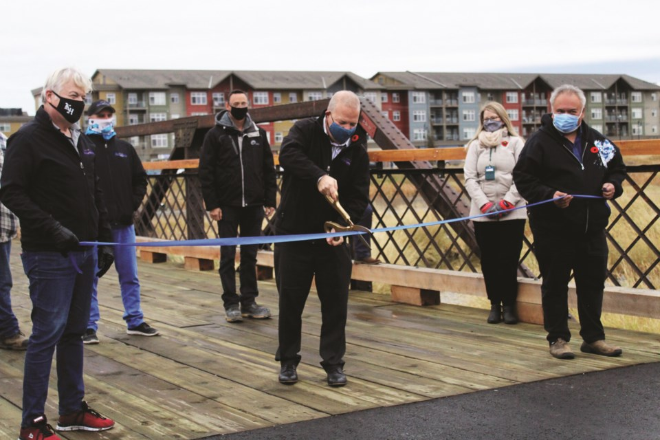 Airdrie Mayor Peter Brown cuts the ribbon at the official completion ceremony for the 1928 Nose Creek Bridge to the Elevators restoration project. Photo by Scott Strasser/Airdrie City View.