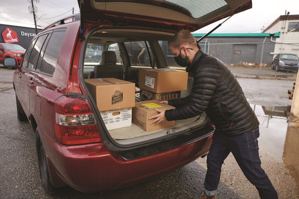 A volunteer with the Leftover Foundation loads a vehicle with leftover food goods in order to transport them to be used by those in need.