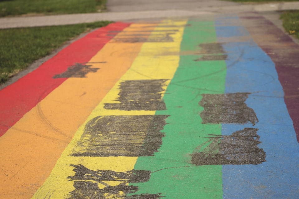Homophobic slurs painted on the rainbow pathway in Nose Creek Regional Park were scratched out by the City. Photo by Scott Strasser/Airdrie City View.