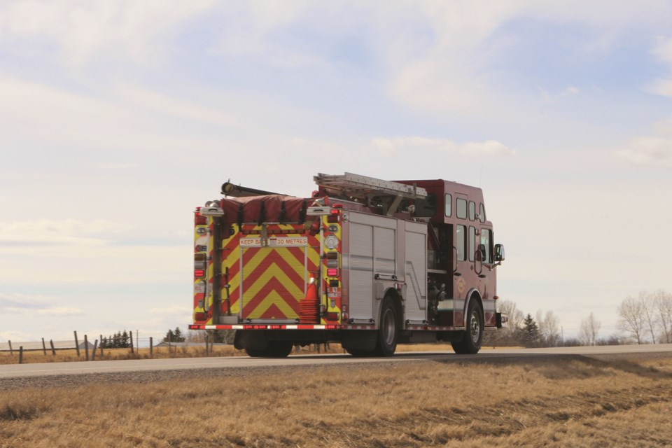 A red fire truck drives down road 566 between Balzac and Kathryn on a Saturday afternoon.