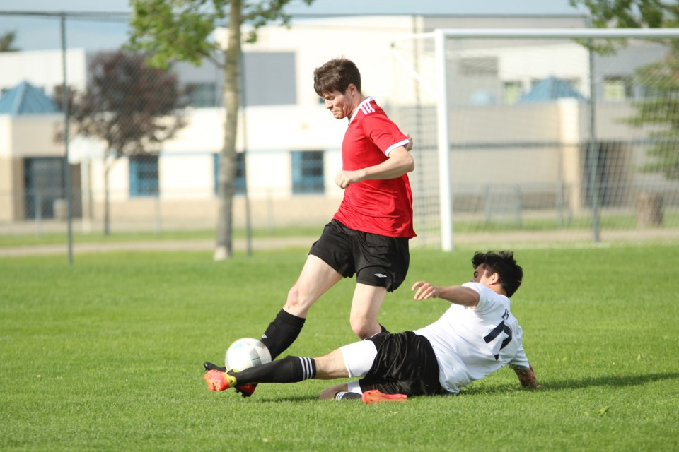 Airdrie United's Tim Roth (white jersey) puts in a slide tackle at Monklands Park July 17 against a Hoods FC player. United lost the game 4-3, despite leading 2-0 at halftime.  Photo by Scott Strasser/Rocky View Publishing