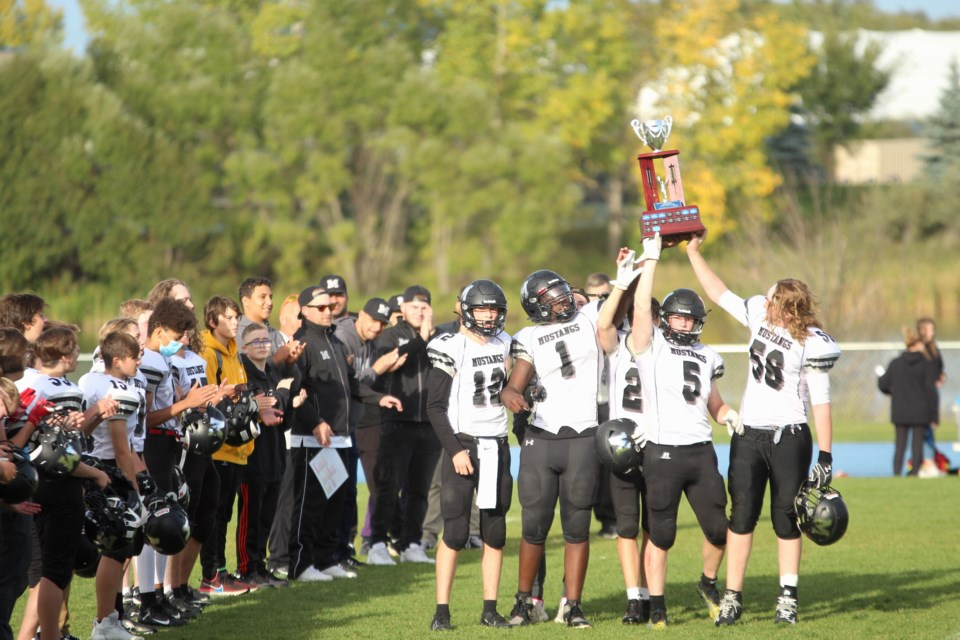 George McDougall's captains lift the Airdrie Bowl trophy after overcoming the Bert Church Chargers 34-3 on Sept. 17. Photo by Scott Strasser/Airdrie City View