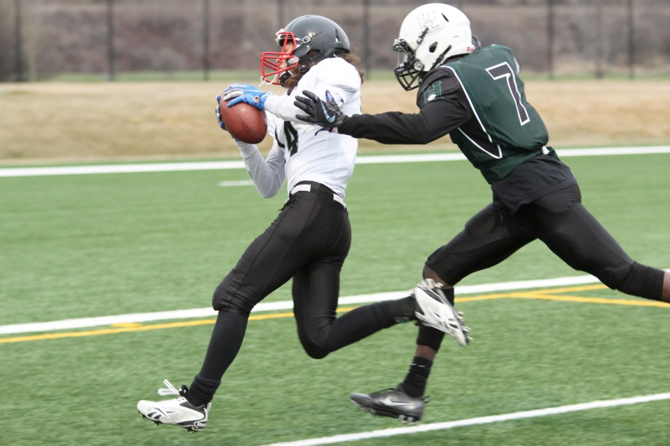 Raiders player Tristan Remus-Arevalo (left) strides towards the end zone for Airdrie's first touchdown against the Calgary Hilltoppers, May 3. The Raiders lost the game 31-12, putting the team at 2-2 in the 2019 CSFA season.  Scott Strasser/Rocky View Publishing