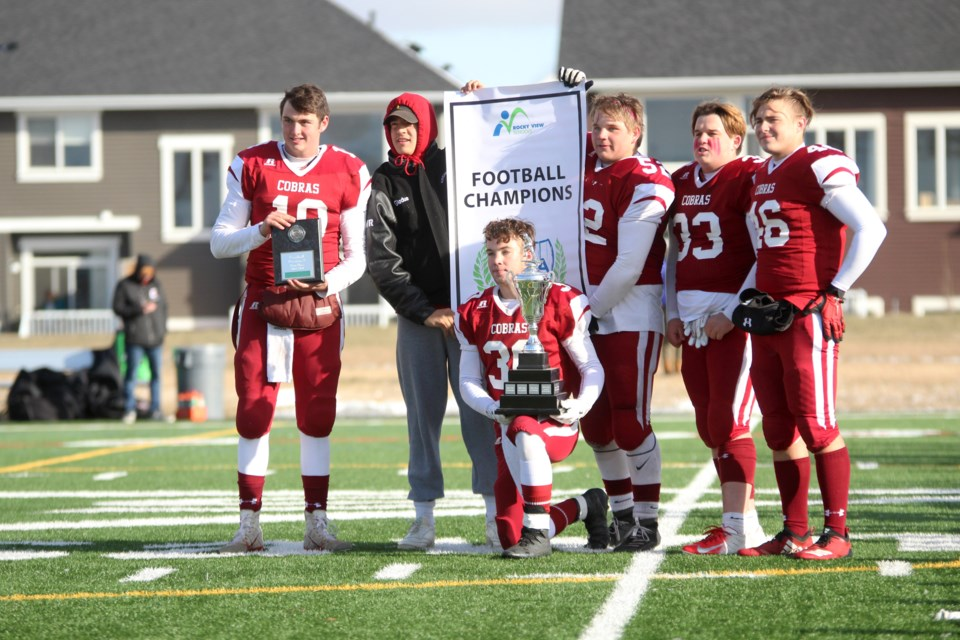 The captains of the Cochrane Cobras football team show off the banner and trophy, after the team secured its fifth consecutive Rocky View Sports Association championship Oct. 26, downing the Bert Church Chargers 31-7. Photo by Scott Strasser/Rocky View Publishing