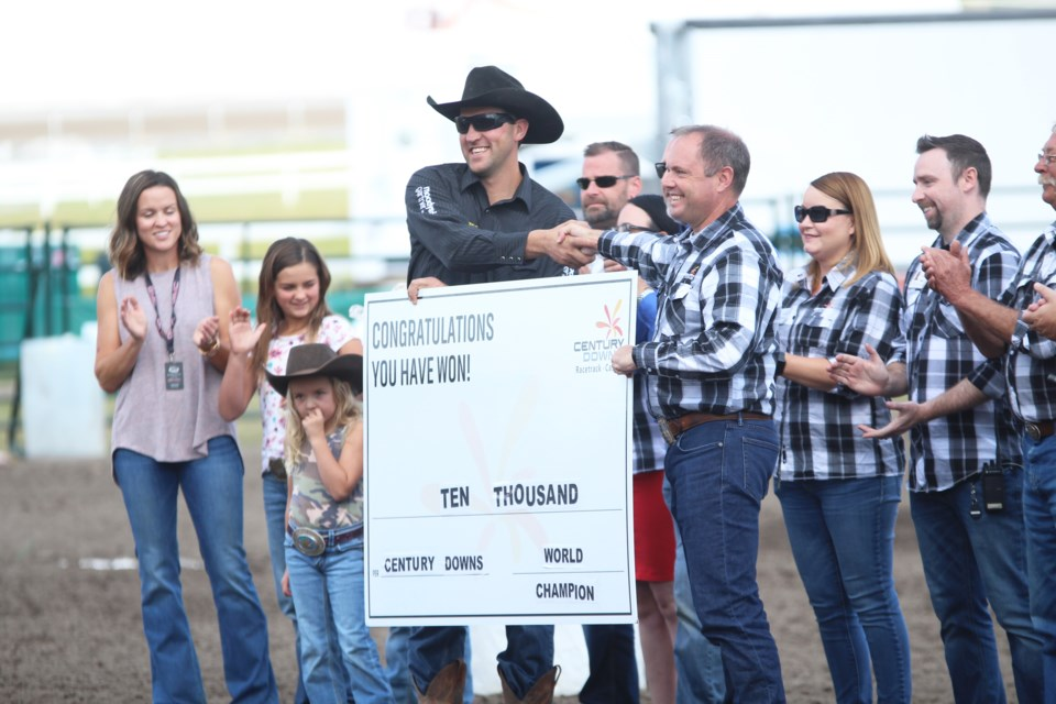 Kurt Bensmiller is presented with the $10,000 cheque by Century Downs Racetrack and Casino General Manager Paul Ryneveld after winning the WPCA's 2019 Pro Tour. This marks Bensmiller's fourth world title in the sport of chuckwagon racing. Photo by Scott Strasser/Rocky View Publishing