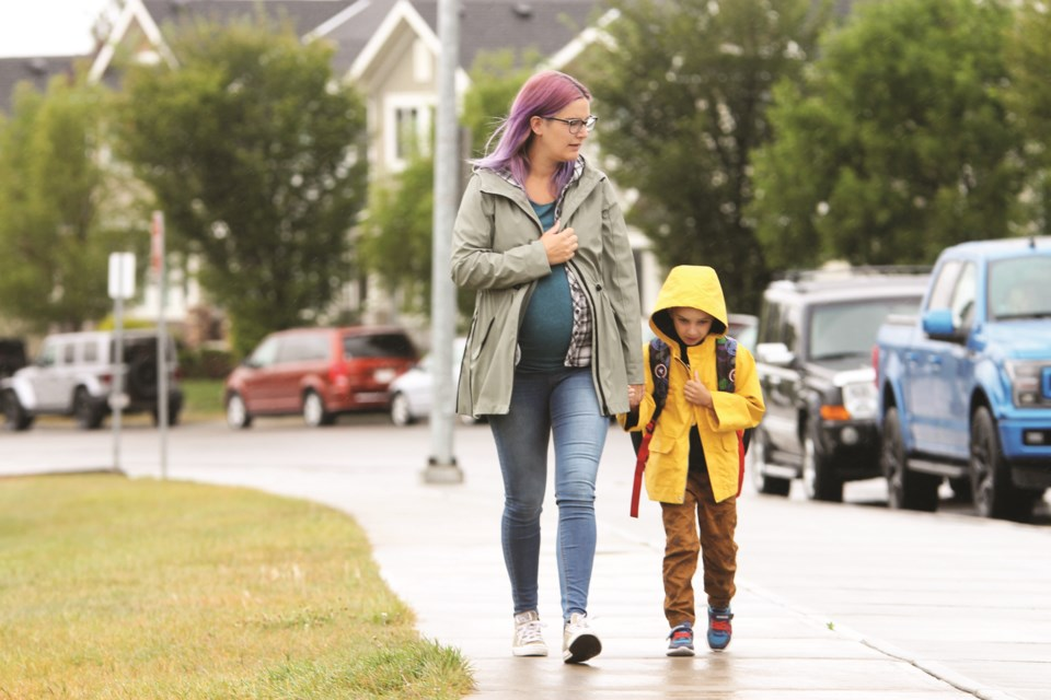 A mother walks her child to Heloise Lorimer School Sept. 2, on the first day of staggered class opening. Schools in Airdrie welcomed back students on three separate days Sept. 2 to 4. Photo by Scott Strasser/Airdrie City View.