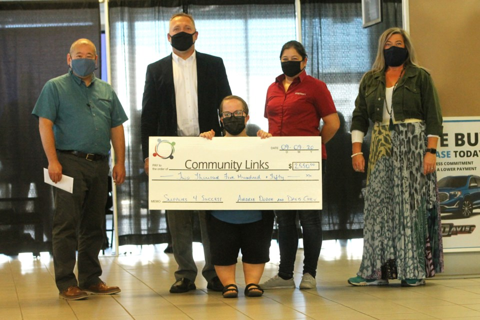 After pledging to donate $10 per vehicle sold in the month of August, Airdrie Dodge and Davis Chevrolet presented a cheque Sept. 9 totaling $2,550 to North Rocky View Community Links' Supplies 4 Success program. Photo by Scott Strasser/Airdrie City View.