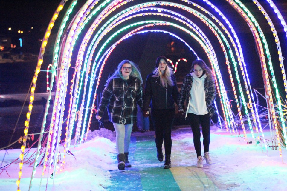 Three girls watch under the arches Dec. 1, during the opening night of the 2019 Airdrie Festival of Lights. The Christmas light spectacle will be shining nightly at Nose Creek Park until the end of December. Photo by Scott Strasser/Rocky View Publishing
