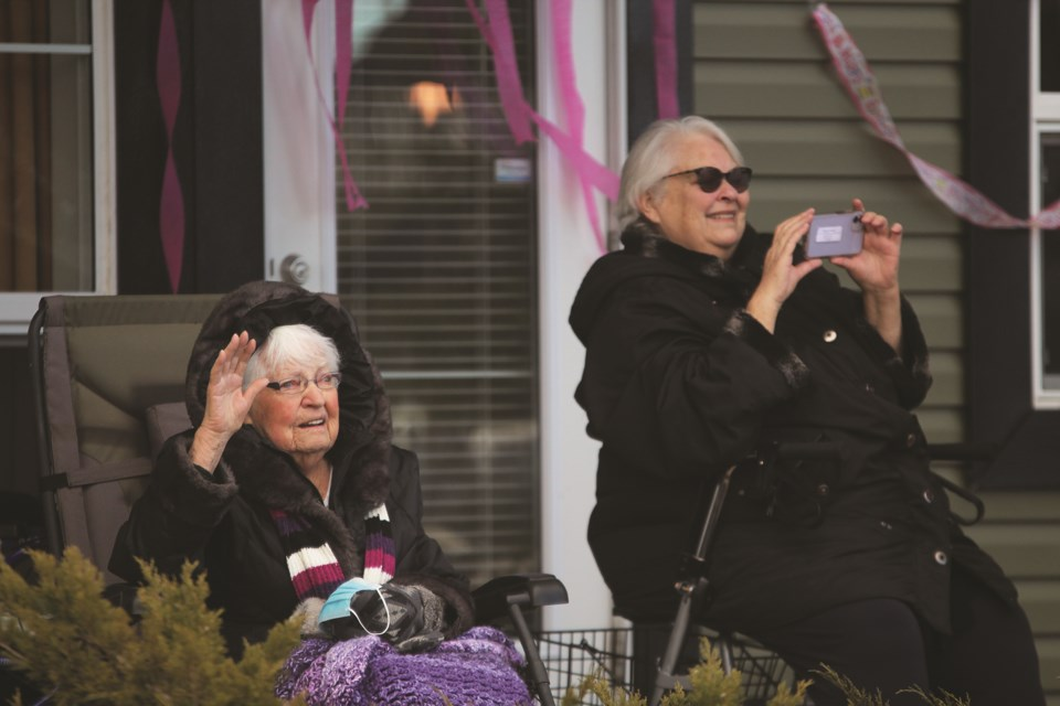 Sagewood resident Pat Van der Zouwen (left) waves from her balcony to a procession of family and friends, who had arranged a drive-by parade to wish her a happy 90th birthday on Jan. 17.