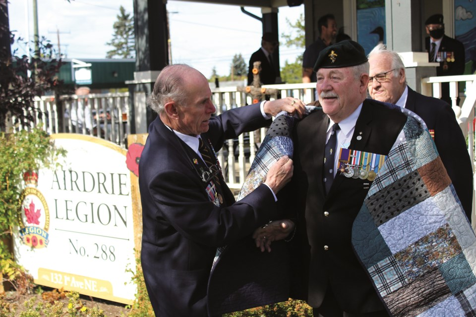 Retired Lt.- Col. Al Price (right) receives a Quilt of Valour Sept. 24 at Airdrie's Royal Legion Canadian, recognizing his service for the Canadian Armed Forces. Photo by Scott Strasser/Airdrie City View.