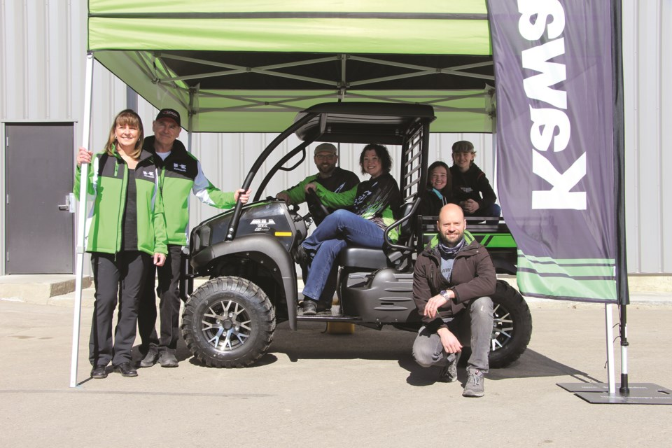 The first-place winners of Beiseker's 2021 Centennial raffle pose in their new Kawasaki Side x Side on March 20 alongisde Ralph Motorsports and Kawasaki representatives.