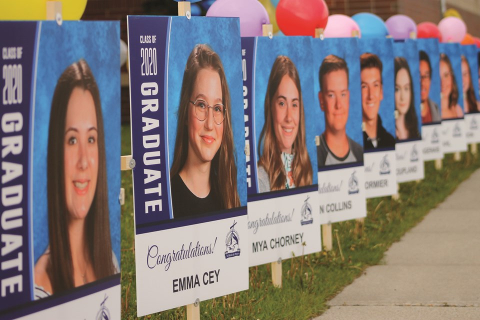 Grade 12 students at St. Martin de Porres were recognized June 18 with an drive-thru graduation ceremony. Each graduate had their poster displayed at the school, where the Class of 2020 paraded through the parking lot. Photo by Scott Strasser/Airdrie City View.
