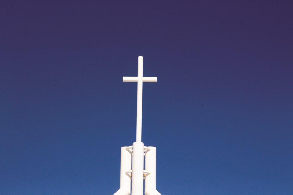 The cross that sits on top of Our Lady Queen of Peace School is backed by a cloudless sky on Feb. 13. Photo by Jordan Stricker/Airdrie City View