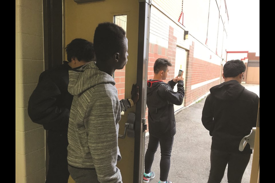 Four students at St. Martin de Porres High School – recent newcomers to Canada – took a moment to snap photos while witnessing their first snowfall Sept. 27.