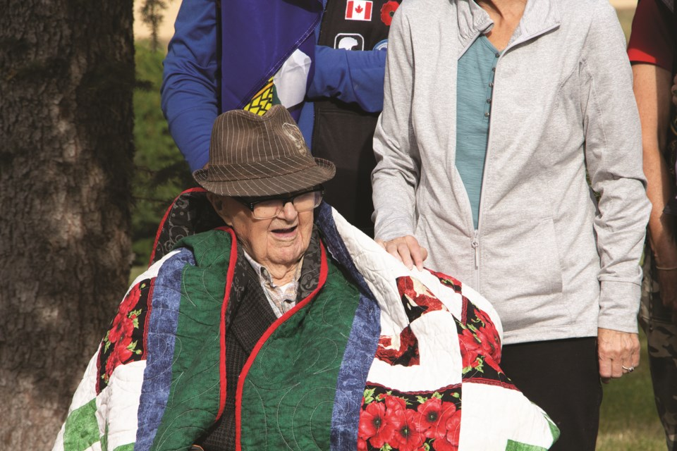 "Bill Ward, a 100-year-old veteran of the second World War, received a Quilt of Valour during a Sept. 21 ceremony at his acreage west of Airdrie. Part of the presentation includes a ""warm hug"" – a moment when family members wrap the recipient in their new quilt. Photo by Jordan Stricker/Airdrie City View"