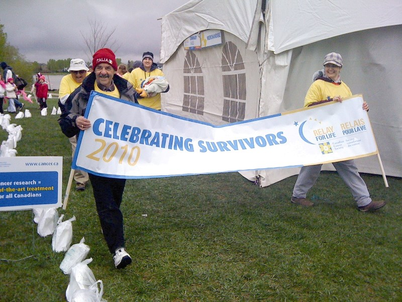 Cancer survivors walk the first lap at the second annual Canadian Cancer Society Relay for Life in Airdrie, May 28. About 175 residents braved the cold, rain and snow to show