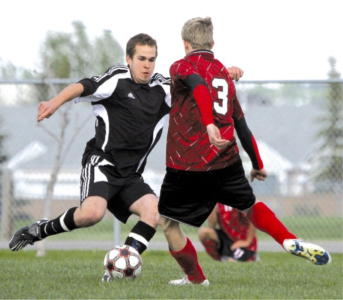 George McDougall's Steven Phee looks to move the ball against this Chestermere defender in the Rocky View Sports Association soccer final held at Monklands Soccer Park