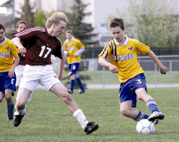 Cochrane Cobra Josh Denison defends against Bert Church Charger Dan Chevrier during the bronze medal match of the Rocky View Sports Association varsity boys soccer playoffs,