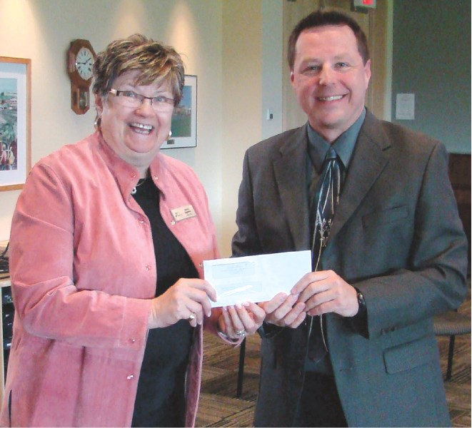 Rocky View Schools Board Chair Sylvia Eggerer accepts a $13,000 cheque from Bruce Daniels, general manager of The Range FM, June 3. The radio station is donating the money