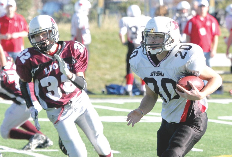 Storm running back Josh Duazo runs by Cochrane's Scott Haigh during Calgary Bantam Football Association playoff action, Oct. 30. Duanzo scored five touchdowns in his