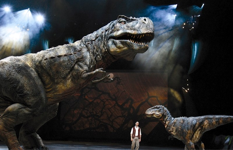 An adult Tyrannosaurus Rex and offspring with the narrator Huxley in a scene from Walking With Dinosaurs – The Arena Spectacular.