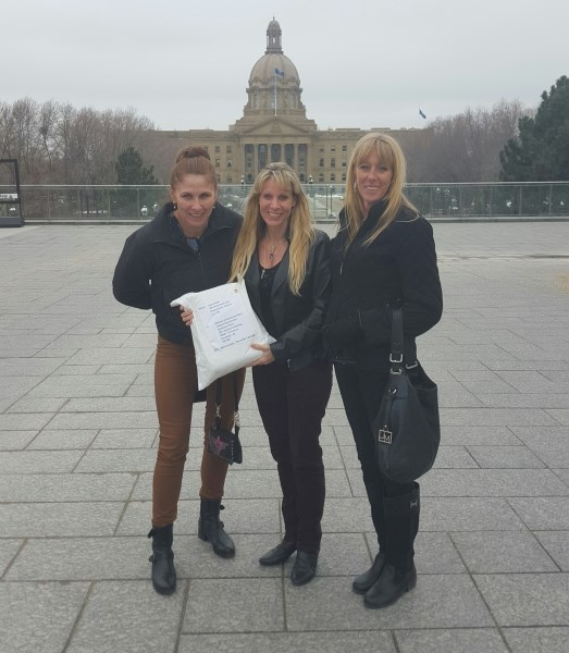 Chestermere residents (from left to right) Judy Dougan, Laurie Bold and Lara Sigurdsen delivered a petition signed by more than 5,000 residents concerned with council to