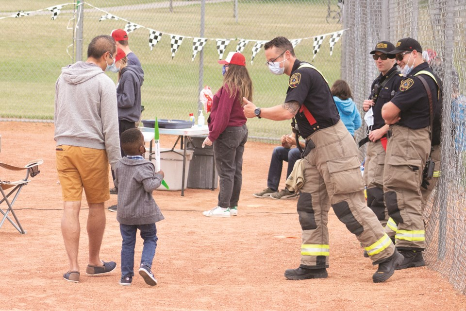 A local Chestermere firefighter cheers on a participant as he walks to the launch pad during Lake Ridge Community Church's rocket derby event in Chestermere Sept. 19. Photo by Jordan Stricker/Rocky View Weekly