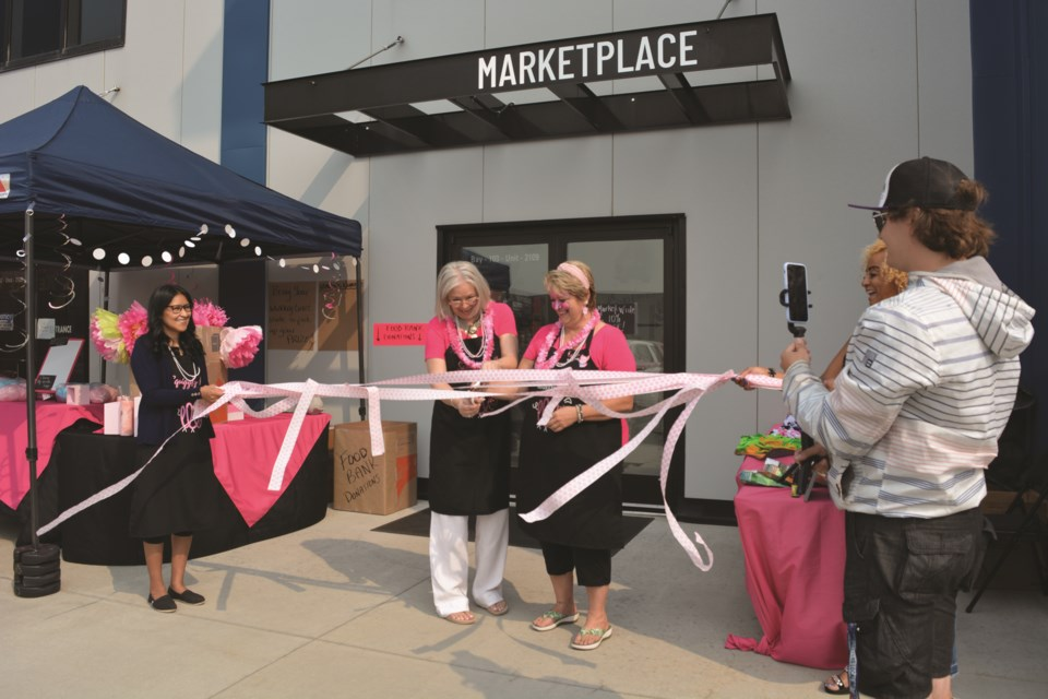 The owners of Squiggly Pig Market grin while cutting the ribbon to celebrate their official grand opening on Aug. 7.
