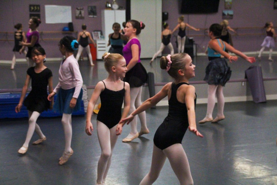 Anna Hogarth, left, and Harvin Lusk follow along to Hannah Mae Cruddas' warmup instructions during a dance workshop at Studio 2 Stage, September 29, 2021.