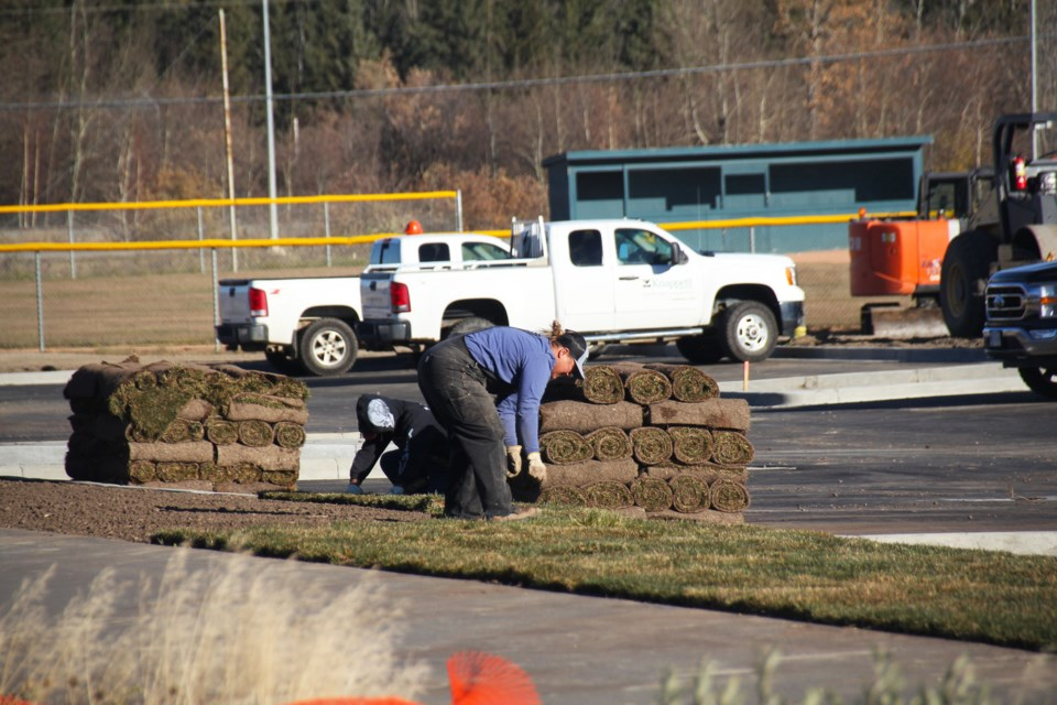 Construction crews lay down sod by the new parking lot at Kin Park, as construction on the West Phase continues, October 13.