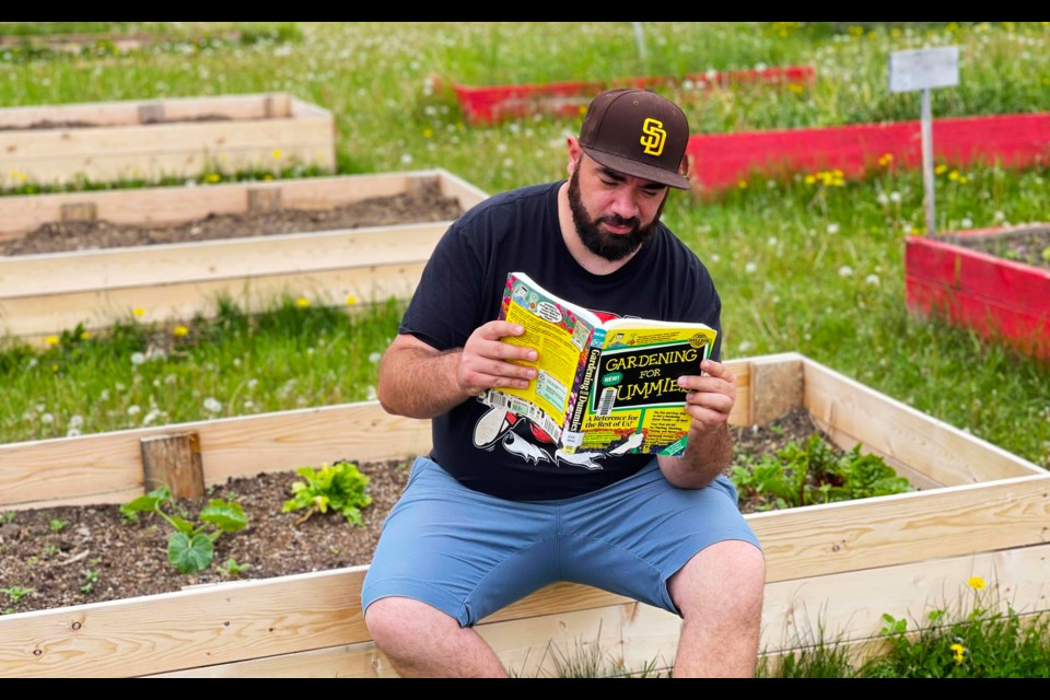 Dillon Giancola reads Gardening for Dummies for a couple tips before tending to his veggies.