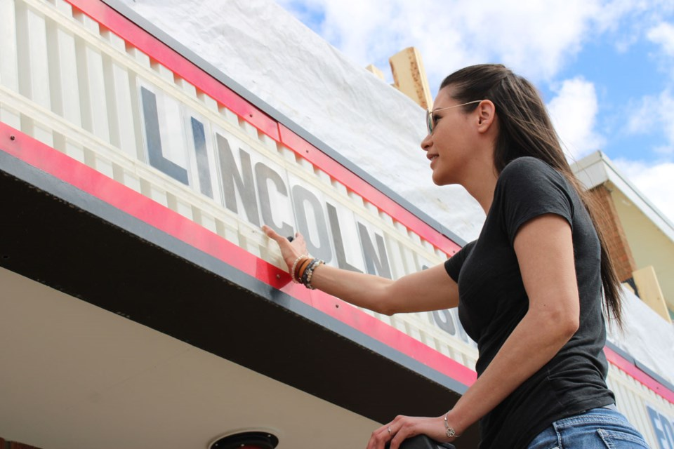 Ashley Prestley hangs lettering in the marquee at the Lido, which has started listing birthdays in exchange for charity donations to the Fort St. John Firefighters Medical Travel Fund.