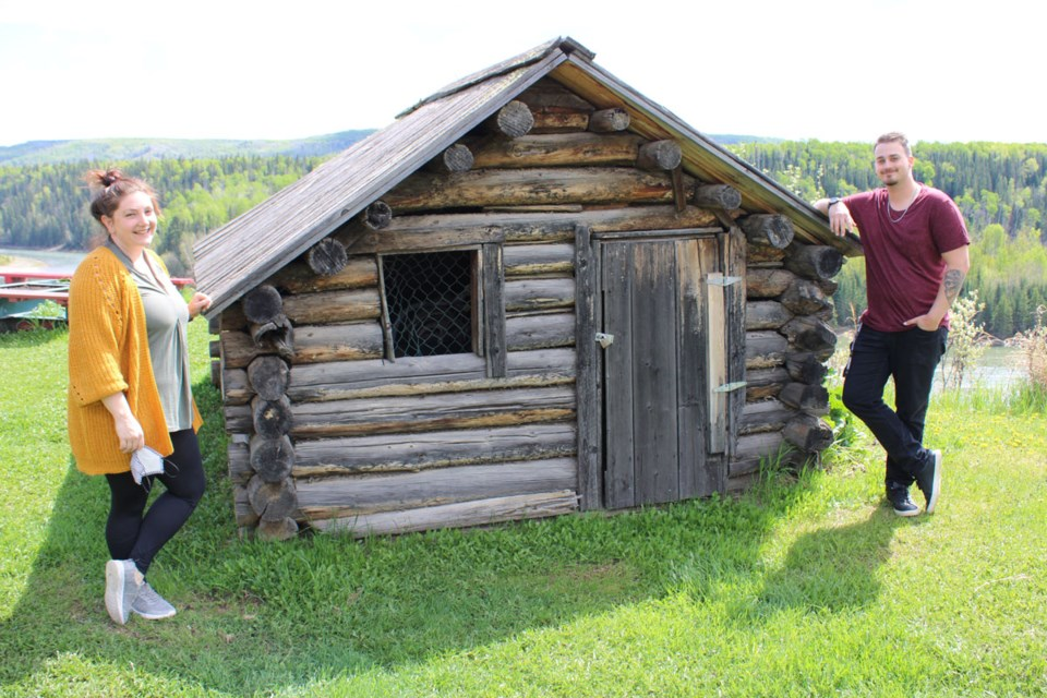 Curator Elinor Morrissey and summer student Joey Poirier in front of one the cabins on display at the Hudson's Hope Museum, which is now open seven days a week.