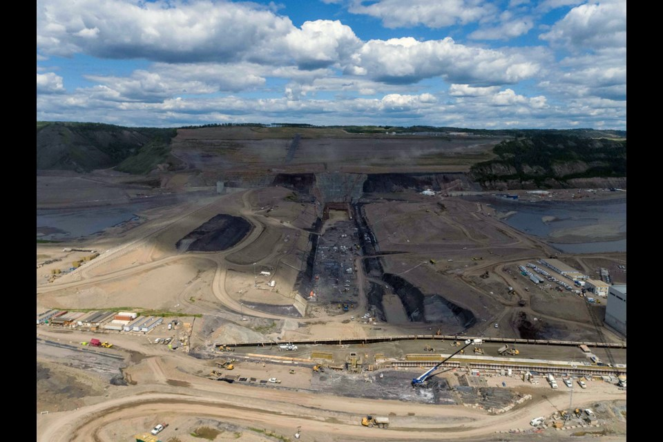 Crews excavate and prepare the dam core area in advance of earthfill dam construction, June 2021.