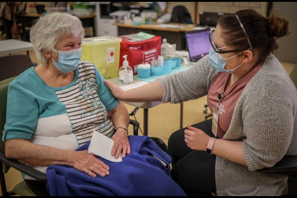 Mary House, 80, receives COVID-19 vaccine from Alyssa Zaderey in Calgary on Feb. 24. Photo: Supplied by AHS.