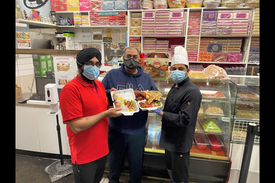 Imran Javaid, centre, and team members display donation-driven meals they have cooked up at Dil-E-Punjab Sweets and Restaurant. Photo submitted